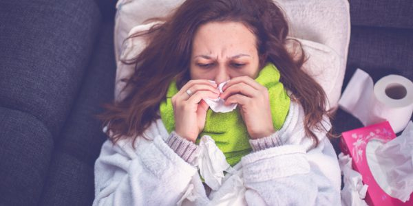 Woman suffering from influenza sleeping in bed